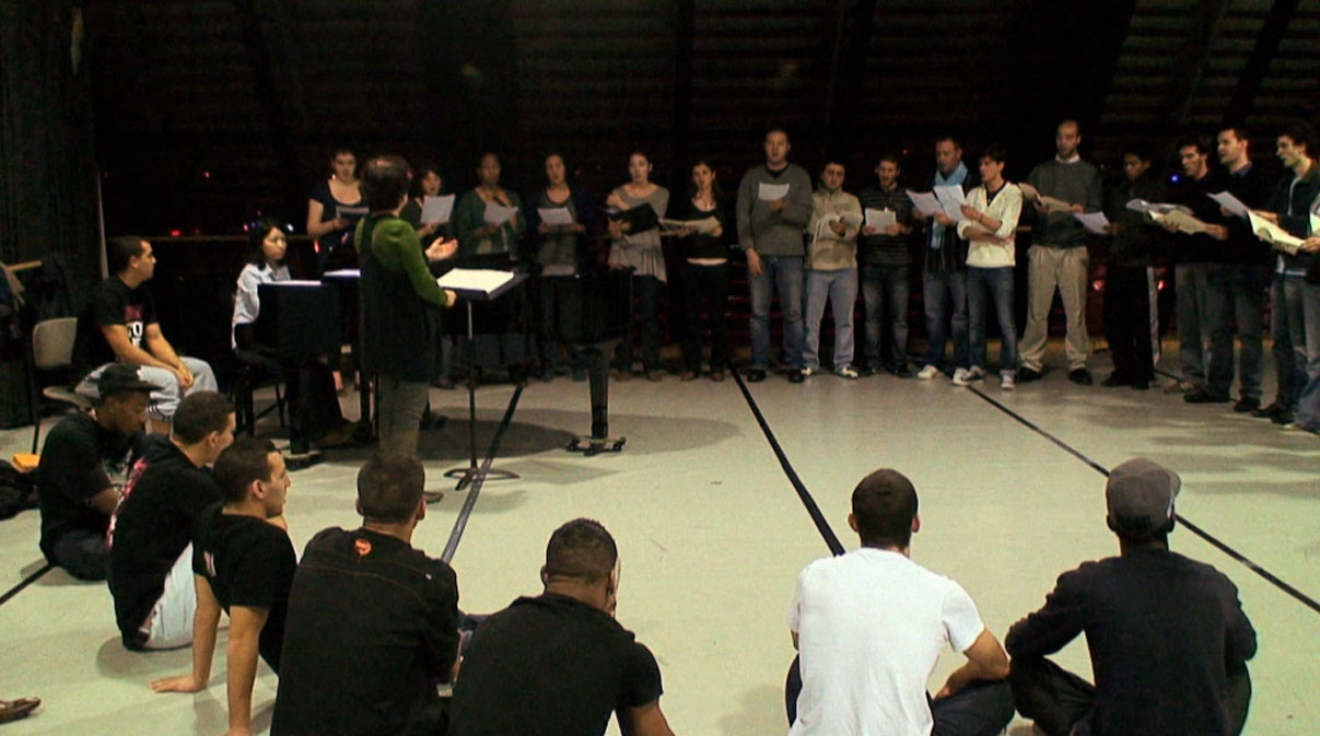 Les danseurs de la Cie Pockemon Crew, assis, écoutent le Choeur Emelthée.
